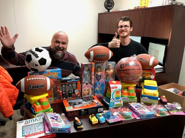 Russell Martinez and David Kaylor having fun with part of FreshPoint Dallas' holiday toy donation to The Family Place.