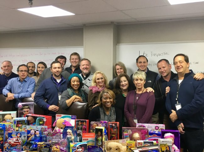FreshPoint Dallas' sales team with part of the holiday donations for The Family Place.