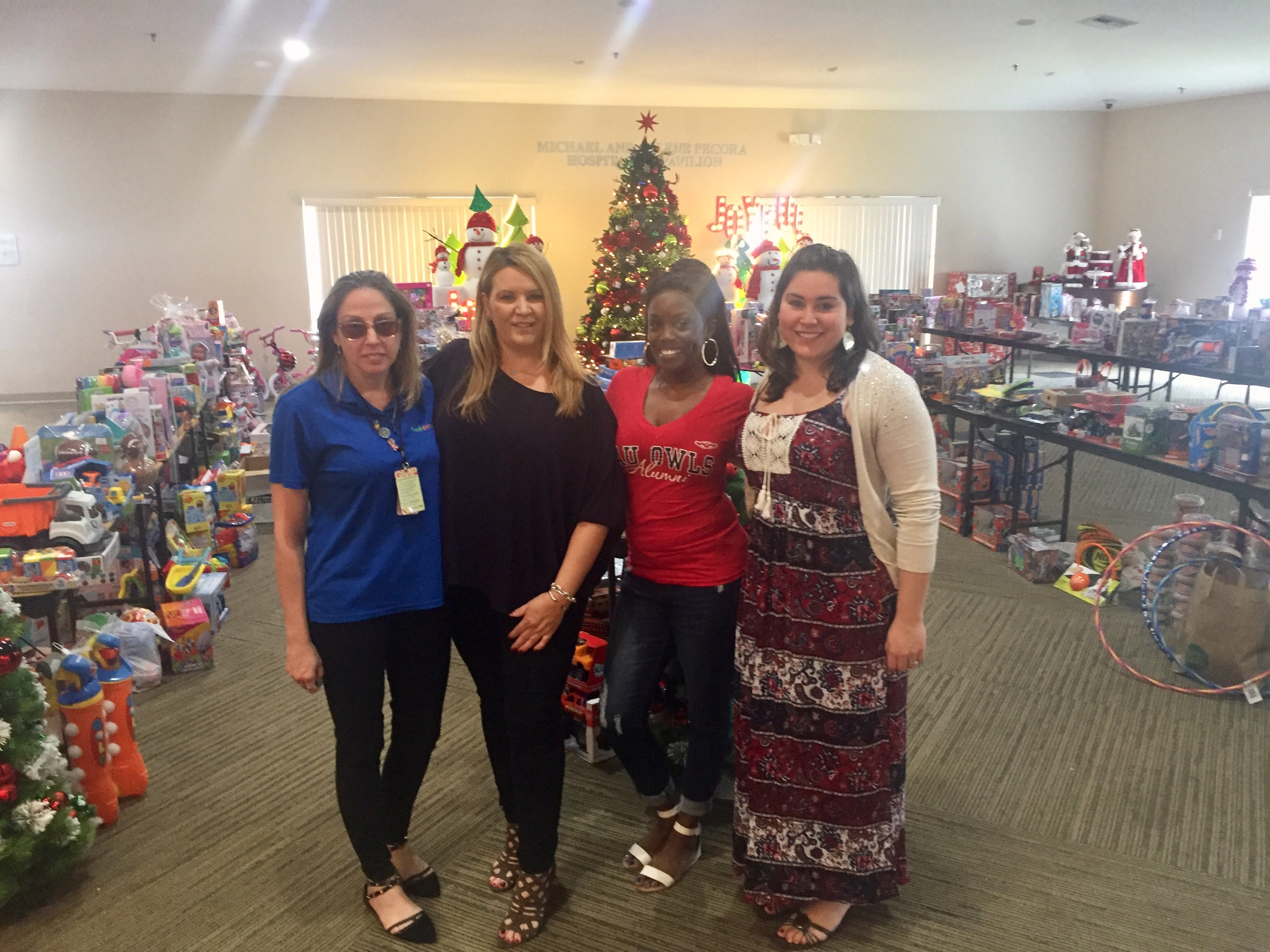 "Jennifer Walls, Kelly Walsh, Janae Watson & Cindy Brunetto in front of the many holiday donations from the community to benefit Women In Distress. They are displayed so the families may go ""shopping."""